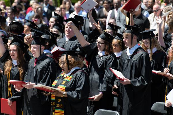 Graduates in audience raise their arms
