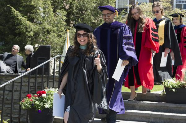 photo of professors in regalia for commencement giving thumbs up