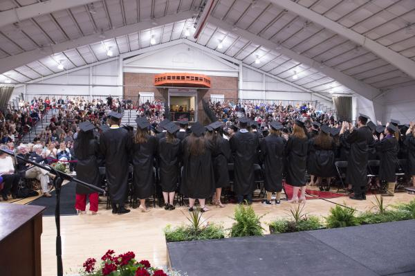 Graduates stand and face the audience