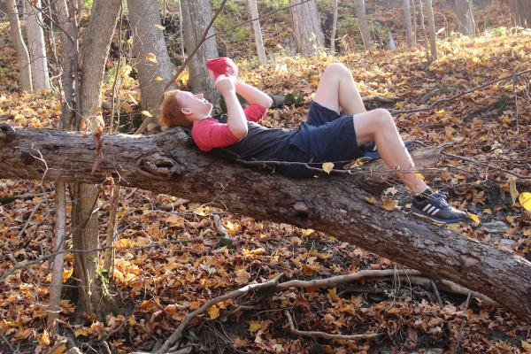 Student laying on downed tree