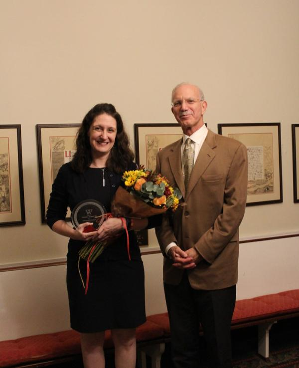 Christin Schaaf holding flowers and standing with President Gibralter