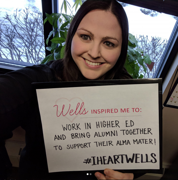 photo of alumna with sign saying wells inspired her to work in higher ed and bring alumni together to support their alma mater