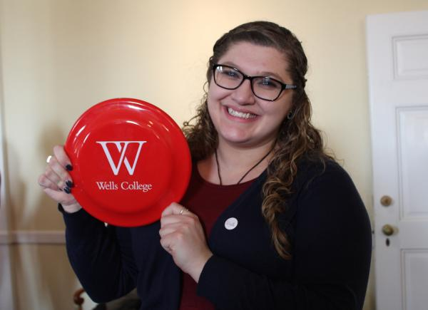photo of staff holding a wells college frisbee