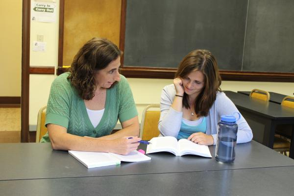 photo of professor working with student in classroom