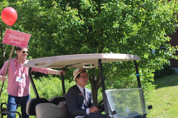 alumni driving golf cart