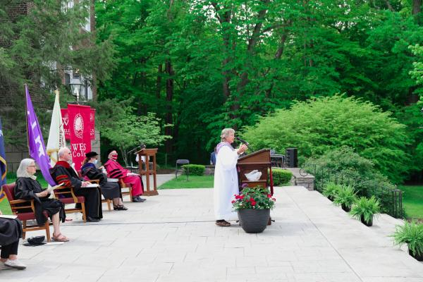 Barb Blom '82 gives invocation while platform party looks on