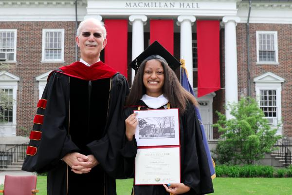 President Gibralter stands with La'Ronica Craven '21 as she shows off her diploma