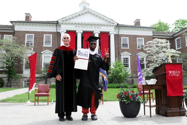 Yomi Russell '21 (right) makes the peace sign and holds his diploma as President Gibralter looks on