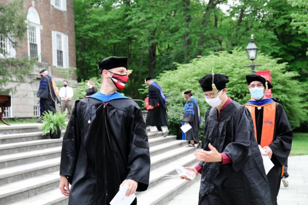 Faculty talk to each other during the recessional at the ceremony's conclusion